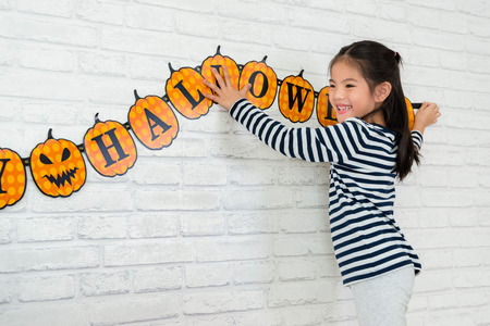 sweet kids help her family to hang up the decoration to celebrate the Halloween holidays at home. Foto de archivo