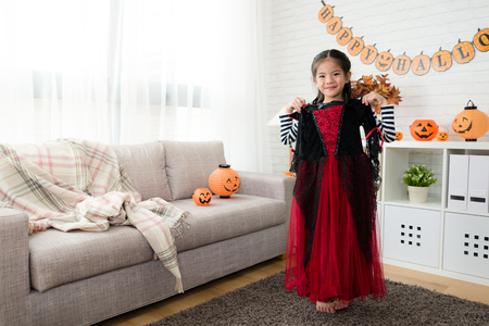 little beauty girl show to try on the Halloween witch dress before the party at home Stock Photo