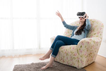 仮想現実を着てソファー椅子に座って若い上品な女性は、オンラインのウェブサイトを探していると、3 D シミュレーション画面を移動する手を使用 写真素材