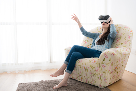 young elegant woman sitting on sofa chair wearing virtual reality goggles looking online website and using hand moving 3D simulation screen.