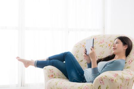 szczęśliwa uśmiechnięta kobieta leżącej na kanapie krzesło przy użyciu mobilnych cyfrowych tabletów i oglądania filmu wideo online relaksu podczas słonecznych wakacji. Zdjęcie Seryjne