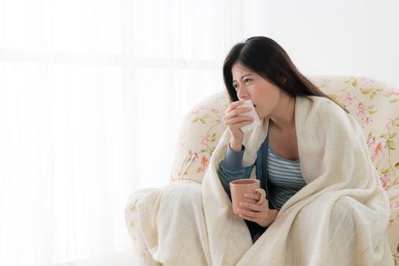 痛みを伴う若い女性は肘掛け椅子のソファの上に座ってリラックスして、病気で咳をします。 写真素材