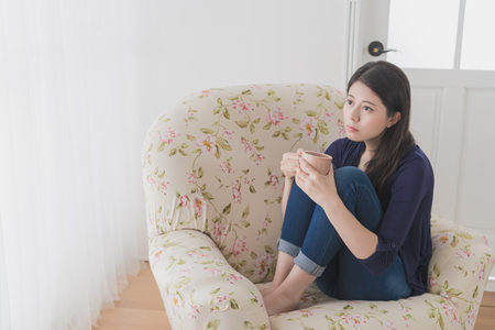 beautiful sad woman feeling depressed looking at window at home and holding hot coffee cup sitting on living room sofa daydreaming.