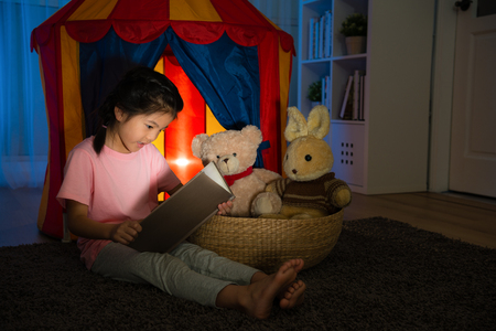 beautiful sweet child sitting in front of kid tent and holding comic book speaking story for her favorite toy on bedroom at night before going to bed.