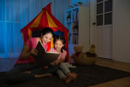 笑顔の女性と夜ベッド ルームに一緒にストーリー漫画を読むグッズ テントの前に座って幸せなゆったりとした子のスリムな。