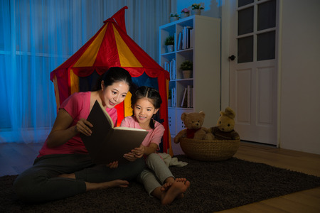 slim smiling lady and happy leisurely child sitting in front of toy tent reading story comic book together on bed room at night.