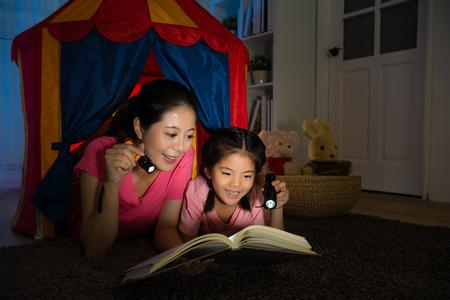 elegante glimlachende moeder met lachende schattige kinderen liggen in speelgoed tent samen en houden zaklamp flitslicht lezen verhaaltje boek 's nachts in bed kamer. Stockfoto