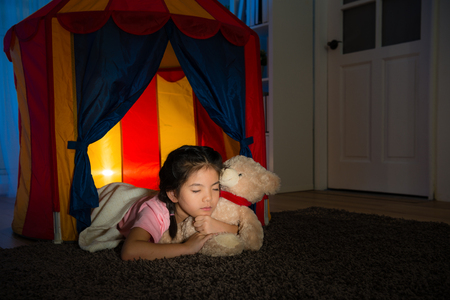 sweet beauty kid lying sleeping in children tent and holding favorite teddy bear toy enjoying good nice dream at night on living room. Stock Photo