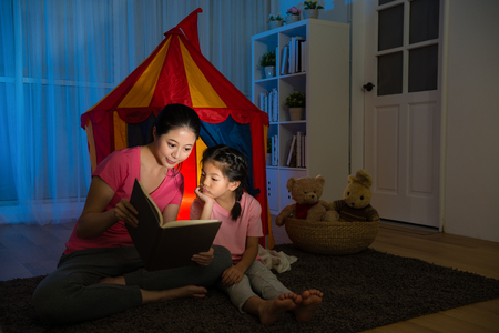 attractive elegant woman sitting on living room floor with beauty calm kid and holding story book together reading at night in holiday vacation.