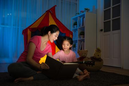 lief aantrekkelijk kind spelen ukulele muziekinstrument kijken naar bladmuziek met elegante slanke moeder zittend op de woonkamer vloer zingen lied voor kinderen tent 's nachts. Stockfoto