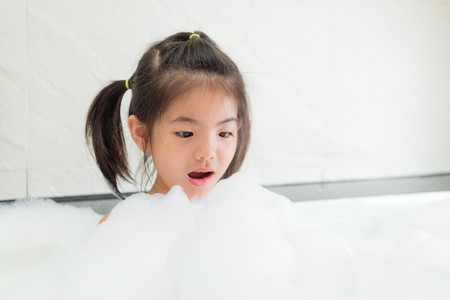 beautiful attractive little girl feeling surprised looking at white bubble when she washing body in bathroom and relaxing on bathtub.