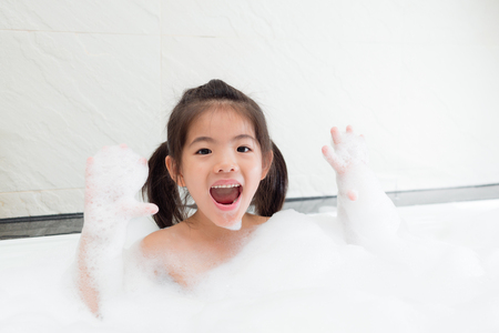 lovely sweet little daughter holding bubble in hands enjoying playing time on bathtub at home and looking at camera laughing.