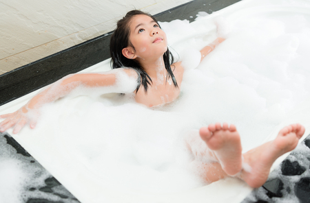 high angle view of beautiful young daughter washing body in bubble bathtub and making relaxing posing daydreaming with selective focus photo.