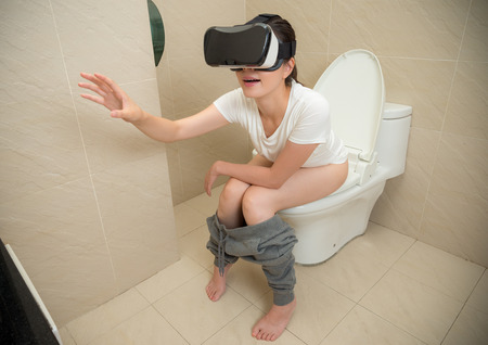 smiling pleasantly woman wearing virtual reality glasses in bathroom and sitting on toilet using VR goggles headset with hand gesture. Stock Photo