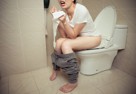 Closeup Photo Of Beautiful Sweet Woman Having Constipation Problem Sitting On Bathroom Toilet Seat And Holding
