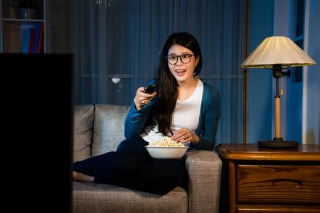 楽しい魅力的な女性は、ポップコーンと選択テレビチャンネルを食べて夜のリビングルームでソファソファに座って面白い映画を探しています。