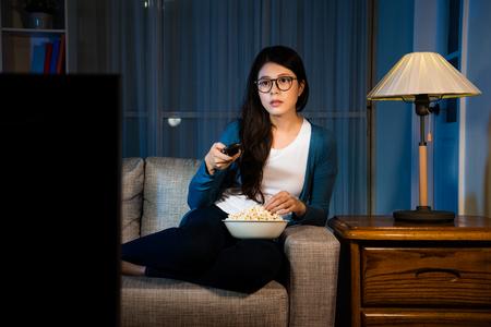 muito doce aluna segurando o controle remoto, olhando para a televisão e comendo lanche delicioso pipoca à noite na sala de estar confortável sofá. Foto de archivo