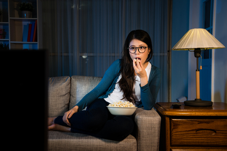 elegant beauty woman looking at television enjoying new movie and eating tasty popcorn snack sitting on living room sofa at holiday night. 免版税图像