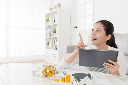 happy beautiful housewife using mobile pad computer daydreaming and pointing air when she having good idea about investing estate. Stock Photo