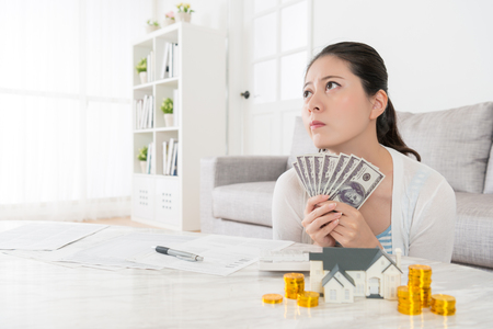 fantasize: happiness attractive housewife daydreaming planning invest buying new house for kids and sitting in living room holding cash counting saving thinking solution.
