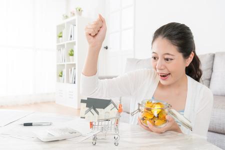 彼女の個人預金を祝う家モデルを見て成功したジェスチャーを作る美しい陽気な少女は、新しいアパートを買うことができます。