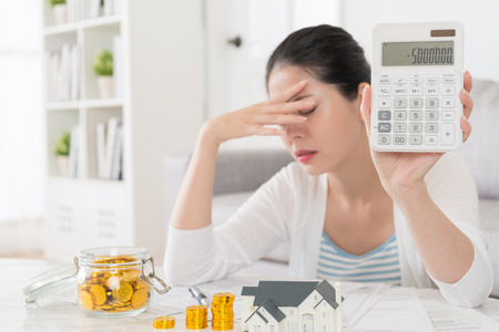 selective focus photo of pretty elegant housewife showing family negative saving number on calculator feeling upset when she planning buying new house. Banco de Imagens - 87810810
