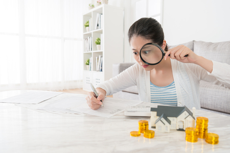 sweet leisurely mother planning saving money to buying new family house and writing everyday spending with holding big magnifier looking at record.