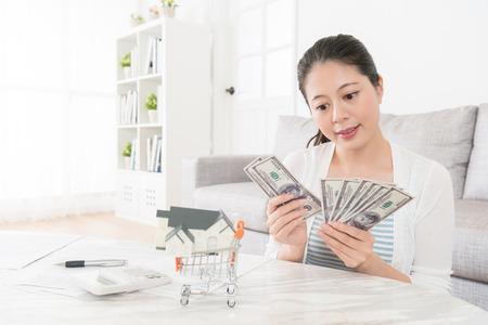 아름다움 매력적인 여자 계산 현금 지폐 거실에서 돈을 예금을 사용 하여 계획 가족을위한 새 집 구입.