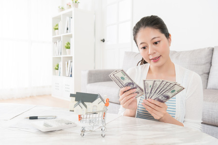 beauty attractive woman counting cash banknote money in living room and planning using deposit buying new house for family.