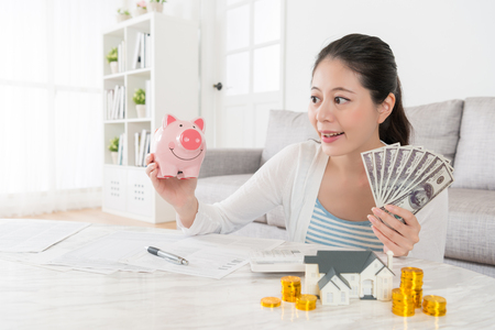 smiling happy female model holding pink piggy bank with cash in living room showing saving money to buying new house for family concept. Stock Photo