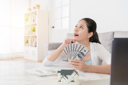リビング ルームと新しい不動産を投資する方法を考えて空想にお金紙幣保存個人カウント幸せな若い主婦 写真素材