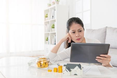 매력적인 우아한 여자 개인 저축 돈을 사용하기로 결정 새 집을 투자 하 고 온라인 부동산 정보를 찾고 모바일 디지털 태블릿 패드 혼란 느낌.