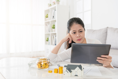 Femme élégante attrayante a décidé d'utiliser l'épargne personnelle d'argent investissant la nouvelle maison et en regardant l'information en ligne de propriété par le biais de tablette numérique mobile se sentant confus. Banque d'images - 87810829