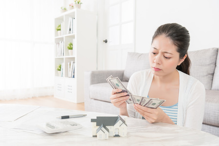 unhappy attractive lady planning investing estate and counting deposit money in living room found fund not enough feeling depressed.