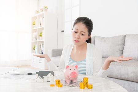 슬픈 아름다운 여인은 가족을 위해 새 집을 사기를 원하지만 그녀의 기금은 충분하지 않고 우울한 저축 느낌을 바라 보는 무력한 포즈를 취하고 있습