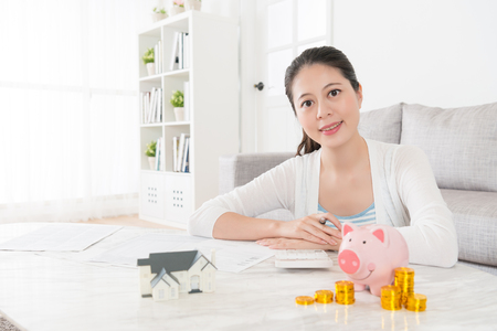 happy attractive right woman face to camera when she calculate spending and saving coin money into piggy bank in order to buy new house for family.