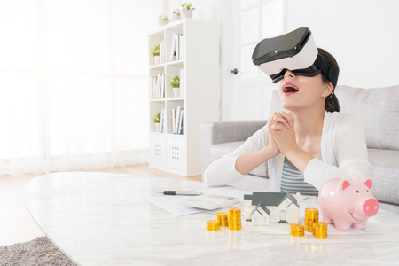 beautiful happy woman looking at 3D architecture video through virtual reality goggles feeling cheerful when she planning buying new house.
