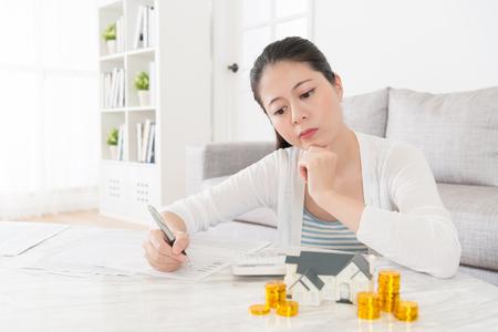 家族についての問題の混乱を持つ若い素敵な主婦保存し、子供のための新しい家の購入支出の思考を記録リビング ルームのデスクに座っています。