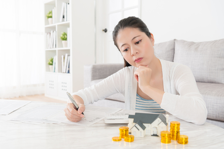 young lovely housewife having confused problem about family save and sitting in living room desk record spending thinking buying new house for kids.