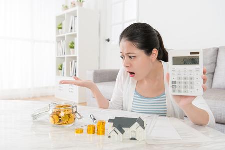 불행 한 젊은 어머니가 그녀가 새 집 계획 및 계산 가족 부정적인 충격을 느끼는 충분하지 않을 때 음수를 보여주는 계산기를 사용합니다.