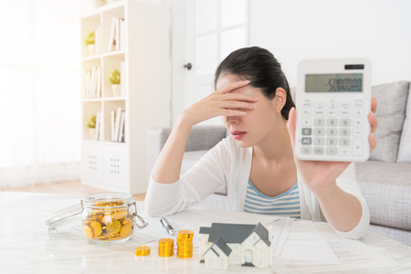 attractive pretty woman using calculator counting personal deposit feeling unhappy because her saving money presenting negative number status. selective focus photo. Stock Photo