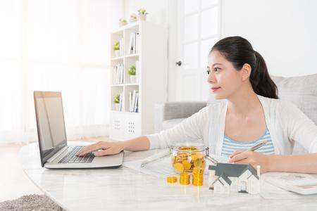 매력적인 아름다움 소녀 모바일 노트북을 사용 하여 자신의 새 집을 구입 계획 개인 온라인 계정 예금 검색. 스톡 콘텐츠 - 87810846