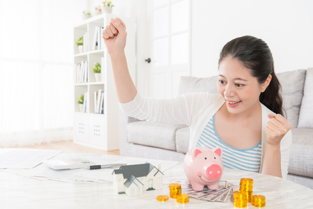 happy smiling woman saving enough fund can buy new apartment and sitting in living room  looking at house model making successful gesture celebration.
