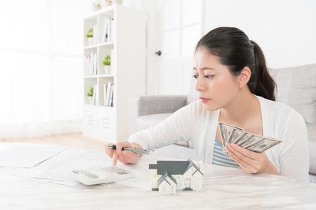 Mujer dulce de la belleza que usa la calculadora que cuenta su billete de banco en la sala de estar , ella quiere celebrar la casa nueva casa para la primavera Foto de archivo - 87811491