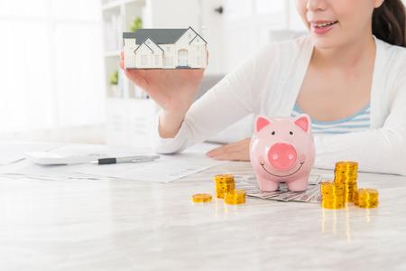 美しさ若い女性小さな家モデルを押しアカウント コイン現金貯金セレクティブ フォーカスの写真と家族のための購入の新しい家を計画をカウントの