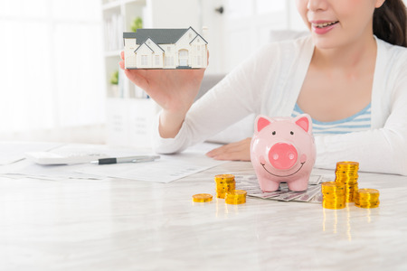 close-up van de schoonheid van de jonge vrouw met kleine huis model en het tellen van rekening munt contant spaarvarken planning kopen van nieuw huis voor familie met selectieve focus foto.