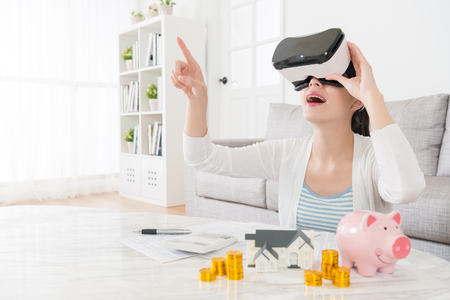 happy elegant mother planning using family deposit buying new house and watching 3D building video information to choosing suitable apartment through virtual reality device. Imagens