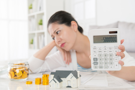 電卓に負の数を示すと混乱を感じて金コインを見て美しいの若い母親のセレクティブ フォーカス写真。