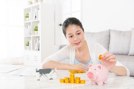 Schöne junge Frau sitzt im Wohnzimmer zu Hause und hält Goldmünze Geld sparen in rosa Sparschwein für den Kauf eines neuen Hauses mit der Familie. Standard-Bild - 87811496
