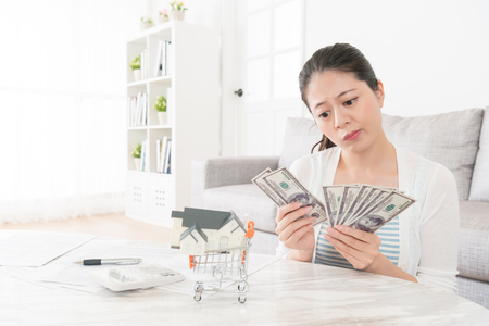 young elegant girl counting savings money in living room feeling sadness because she planning buying new house but deposit not enough.